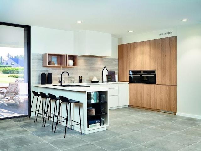 witte keuken met barkrukken spoelbak ovens werblad en groot raam