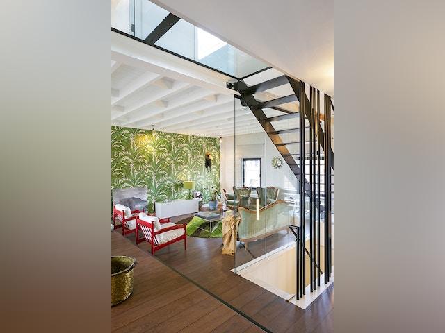 Superposées, les deux volées d'escalier offrent des perspectives quasi théâtrales sur l'ensemble des volumes du duplex, dont le niveau supérieur se trouve sous les combles.
