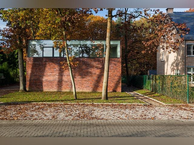 La façade avant n'a de fenêtres qu'au premier étage. Une manière de se couper de la rue sans perdre le contact avec l'environnement boisé.