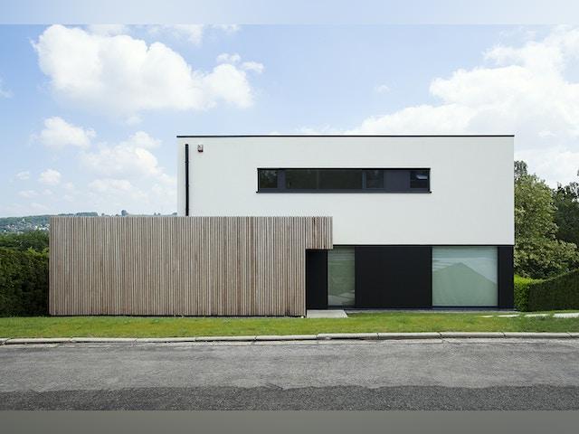 Wit, zwart en hout zetten zuivere geometrische lijnen neer die de hedendaagse architectuur benadrukken.