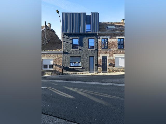 Initialement semblable à ses voisines, cette maison est désormais chapeautée d'une boîte noire bardée de zinc. Une manière de lui donner davantage de volume sans modifier sa hauteur.